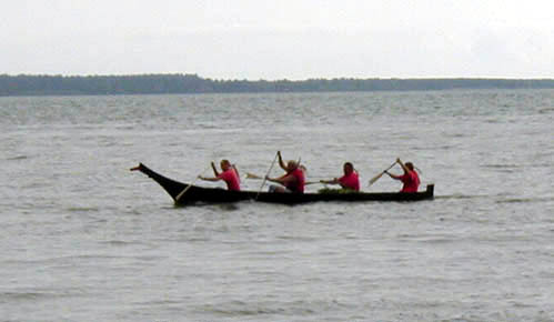 A photo of a taped-seam plywood replica of a Chinook dugout canoe at speed.